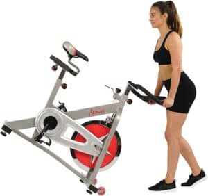 The Sunny Health and Fitness Pro B901 Indoor Cycling Bike is being moved for storage by a lady