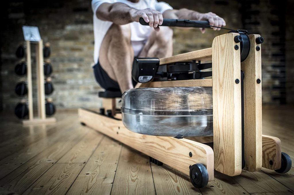 A man is rowing on the WaterRower Natural Rowing Machine with S4 Monitor