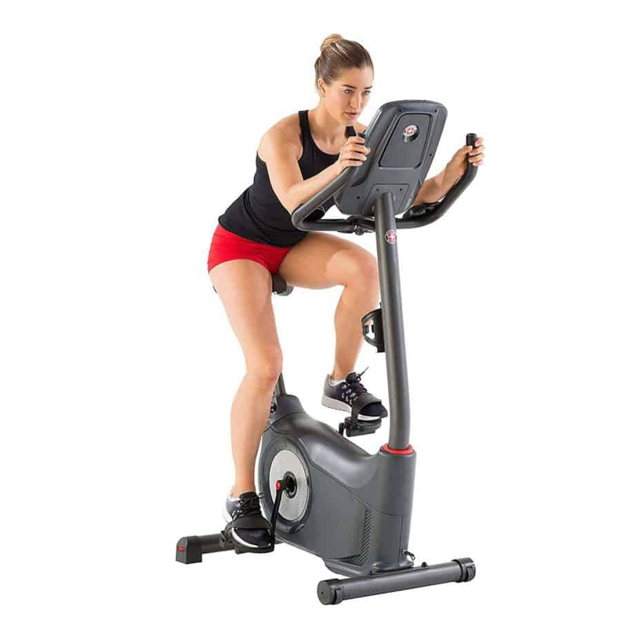 A lady riding the Schwinn 170 Upright Bike is being ridden by a lady