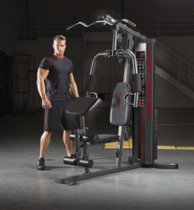 An athlete poses beside the Marcy MWM-990 Home Gym