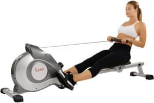 A lady is rowing with the Sunny Health and Fitness SF-RW5515 Magnetic Rowing machine