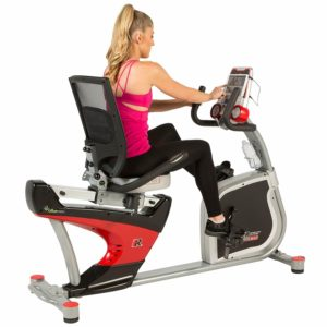 Fitness Reality X-Class 410 Recumbent Exercise Bike is being ridden by a woman