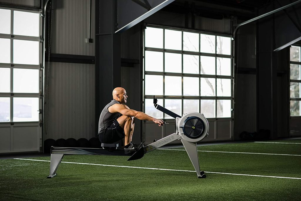 A man is rowing on the Concept2 Model E Indoor Rowing Machine