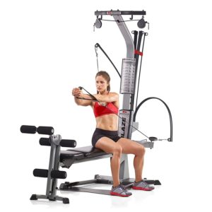 A woman is exercising on the Bowflex Blaze Home Gym