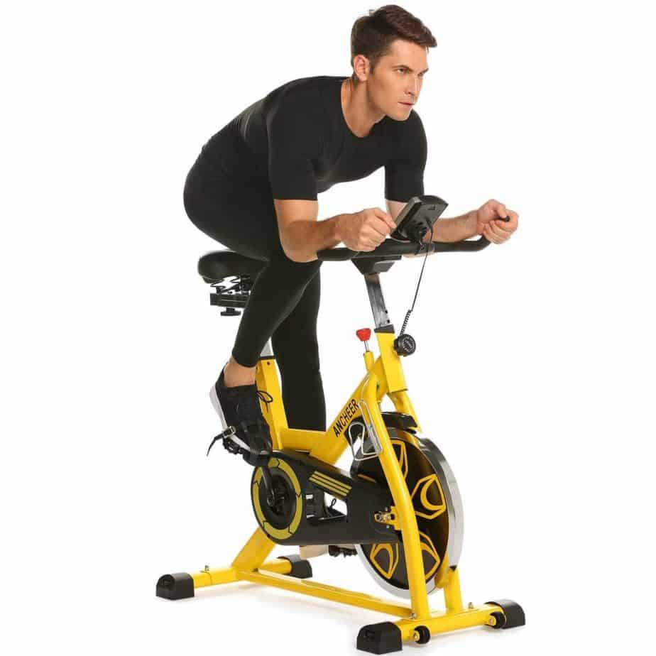 A man is exercisng with the Ancheer Indoor Cycling Bike, Belt Drive B3008