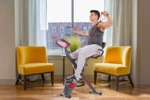PLENY Upright Stationary Semi-Recumbent Exercise Bike with Arms Exercise Resistance Bands is being used by a man