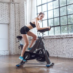 A lady is exercising with the L Now Indoor Cycling Bike LD-577