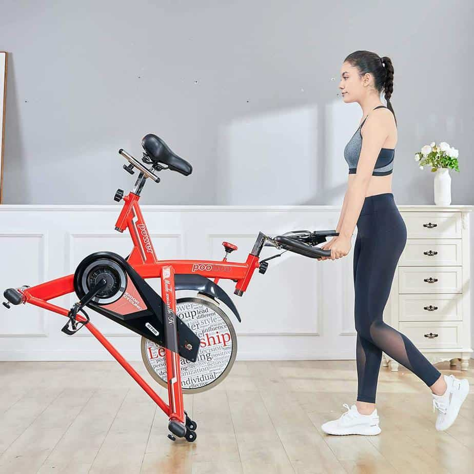 The Pooboo L NOW Indoor Cycling Bike D760 is being rolled away by a lady