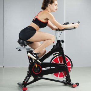 A lady is riding on the Syrinx Indoor Cycling Bike