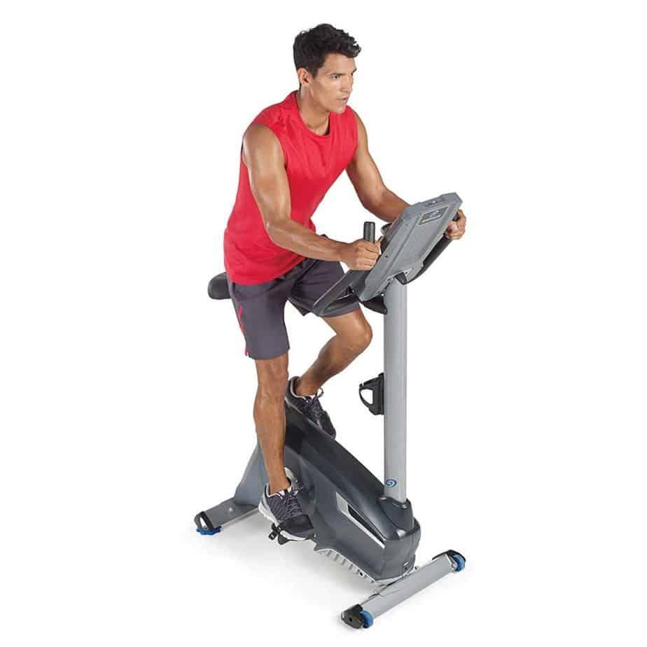 An athlete is exercising on the Nautilus U614 Upright Bike