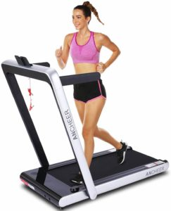 A lady using the ANCHEER 2-in-1 Folding Treadmill with the stands and handlebars up