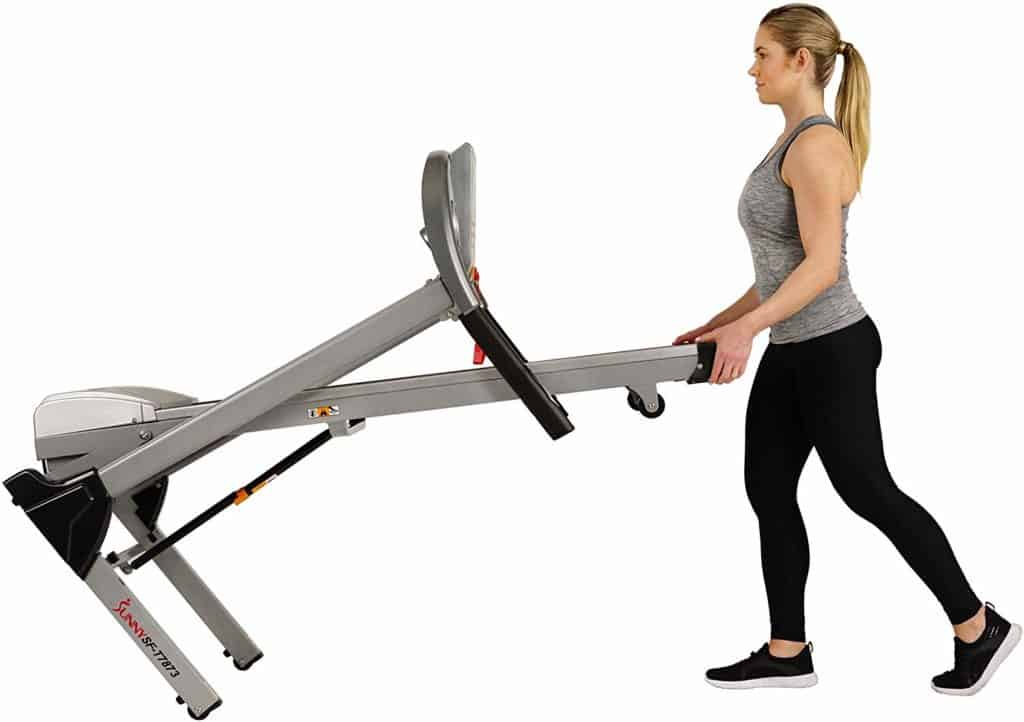 The Sunny Health & Fitness Electric Folding Treadmill SF-T7873 is being moved to storage by a lady