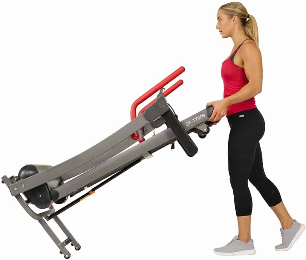 The Sunny Health & Fitness Folding Electric Treadmill SF-T7909 is being moved to storage