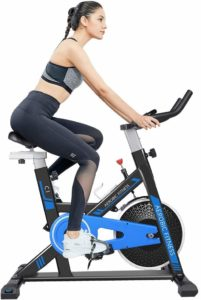 A lady is exercising with the Cycool Belt Drive Stationary Bike (C1)