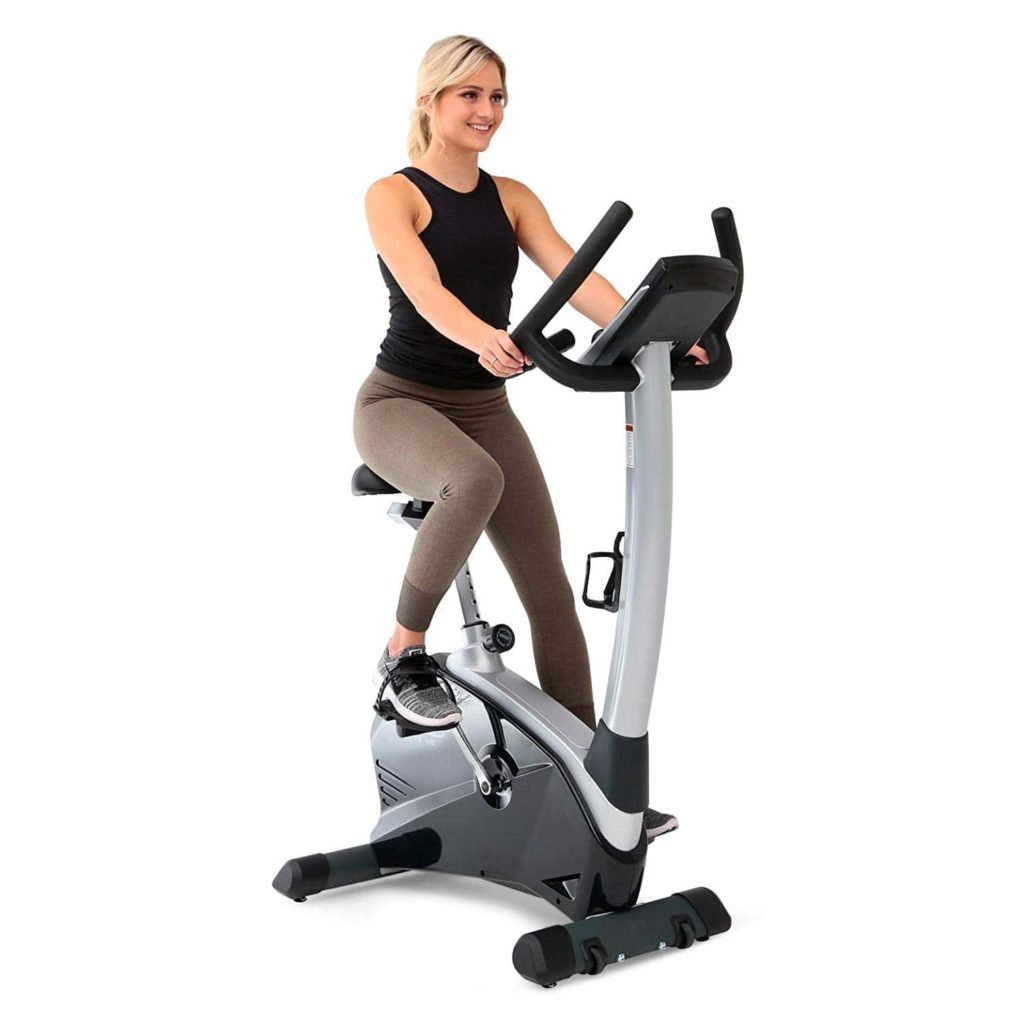 A lady is exercising on the 3G Cardio Elite UB Upright Bike