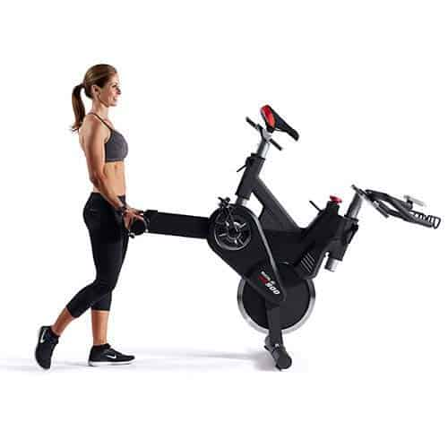 A lady is moving the SOLE SB900 Indoor Exercise Bike to storage