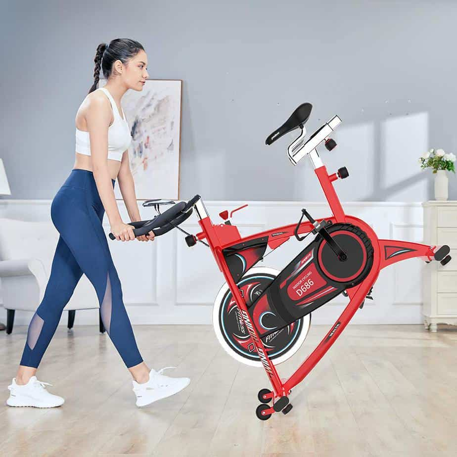 A lady rolls the Pooboo D686 Indoor Cycling Bike away to storage