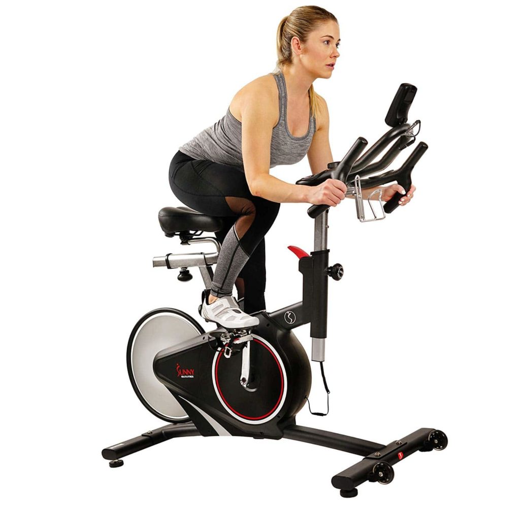 A lady is riding the Sunny Health & Fitness SF-B1709 Indoor Cycling Bike