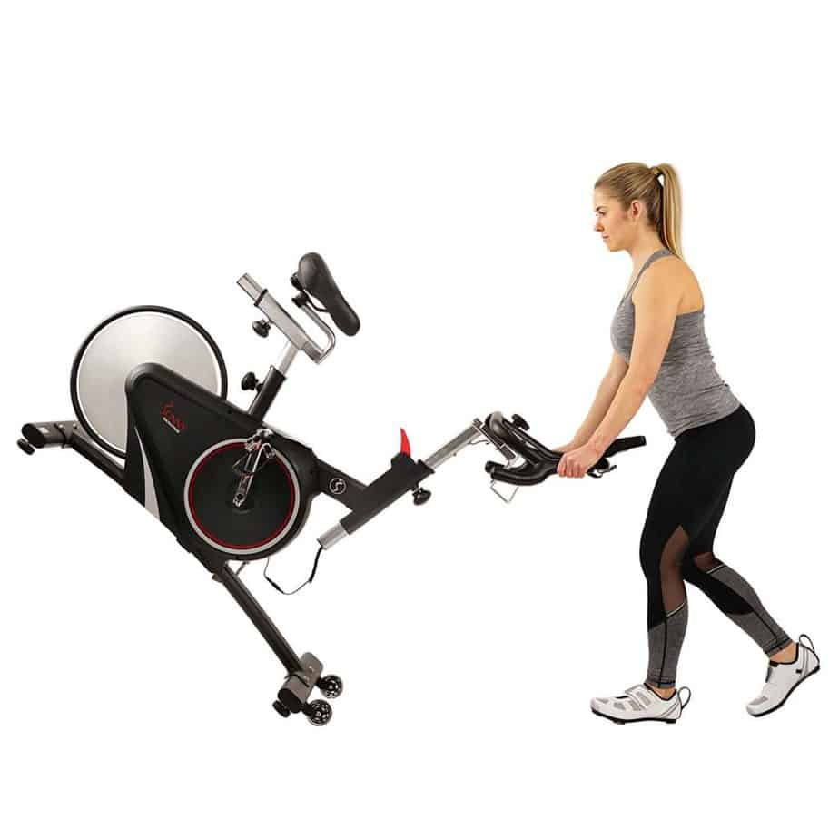 A lady rolling away the Sunny Health & Fitness SF-B1709 Indoor Cycling Bike to storage