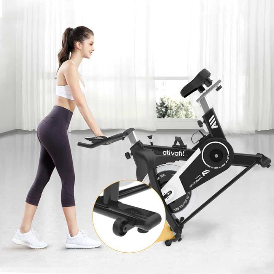 A lady is moving the Ativafit IC-702 Indoor Cycling Bike to storage