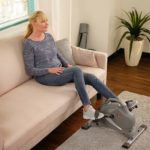 A lady exercising with the Sunny Health & Fitness SF-B0418 Mini Bike while sitting on the sofa