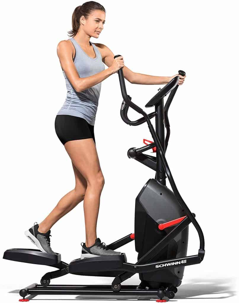 A lady is working out with the Schwinn 411 Compact Elliptical