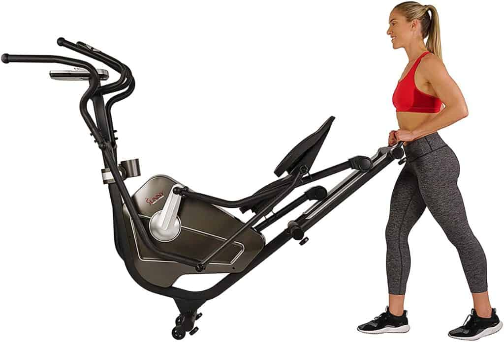 A lady is moving the Sunny Health and Fitness SF-3862 Elliptical to storage
