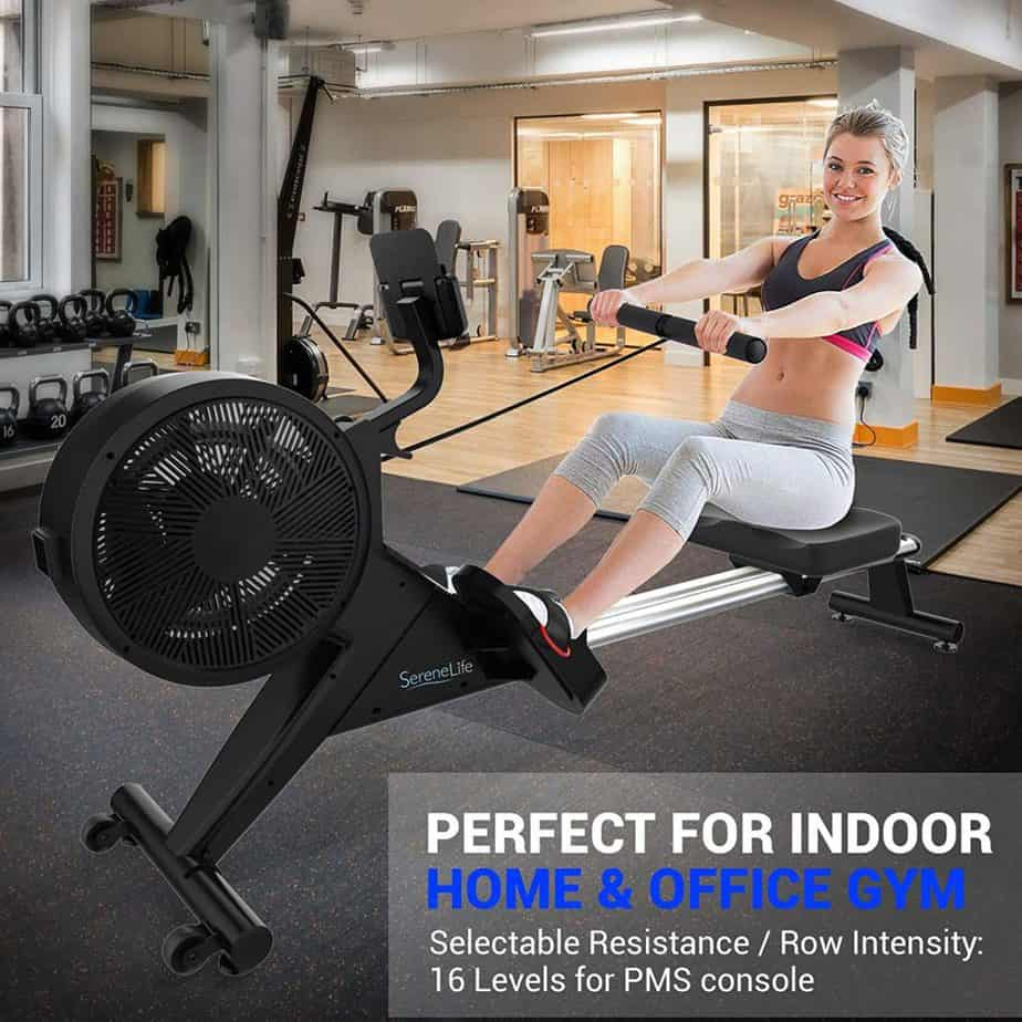 A lady is rowing with the SereneLife SLRWMC60 Smart Rowing Machine at home gym