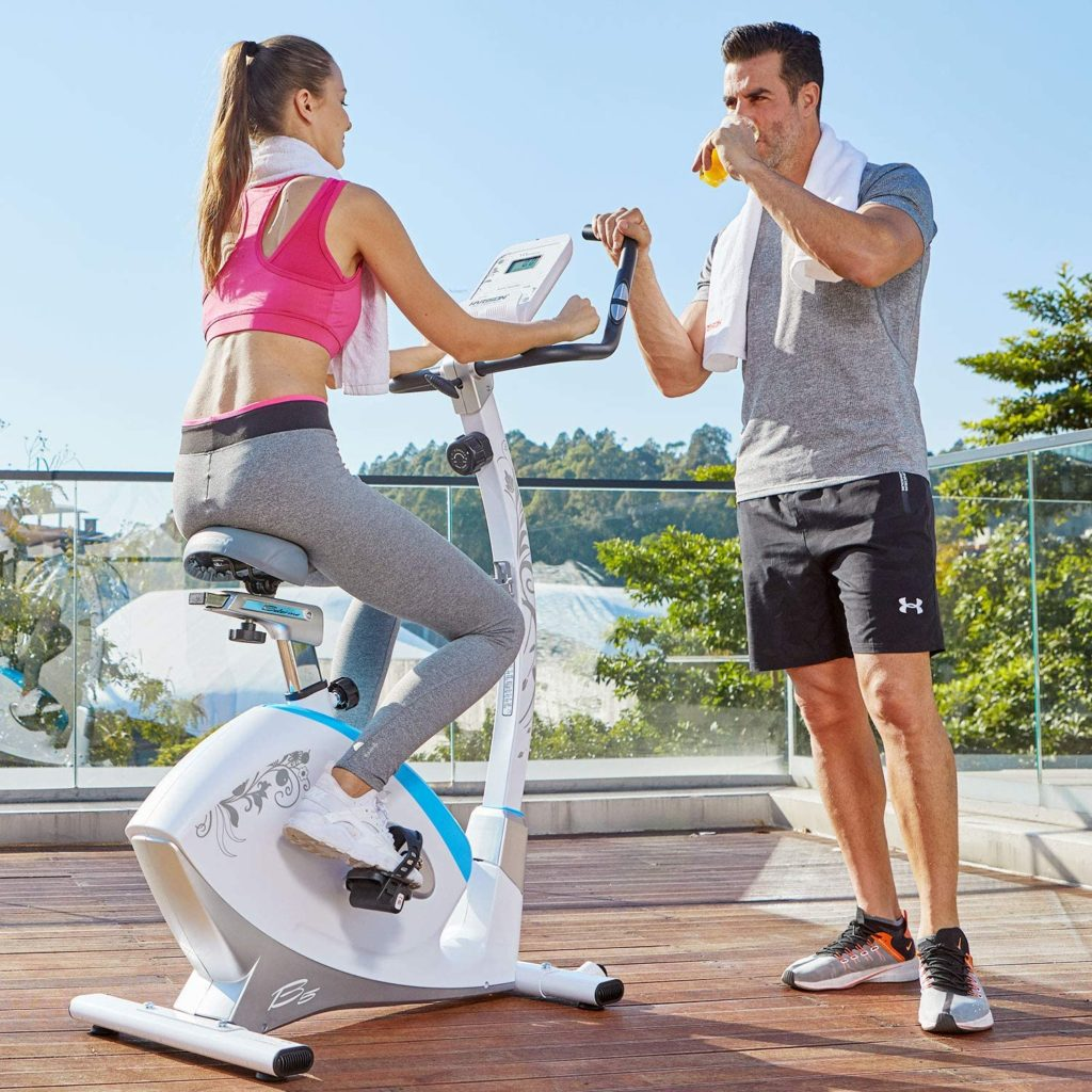 A lady is working out with the HARISON B5 Upright Magnetic Bike
