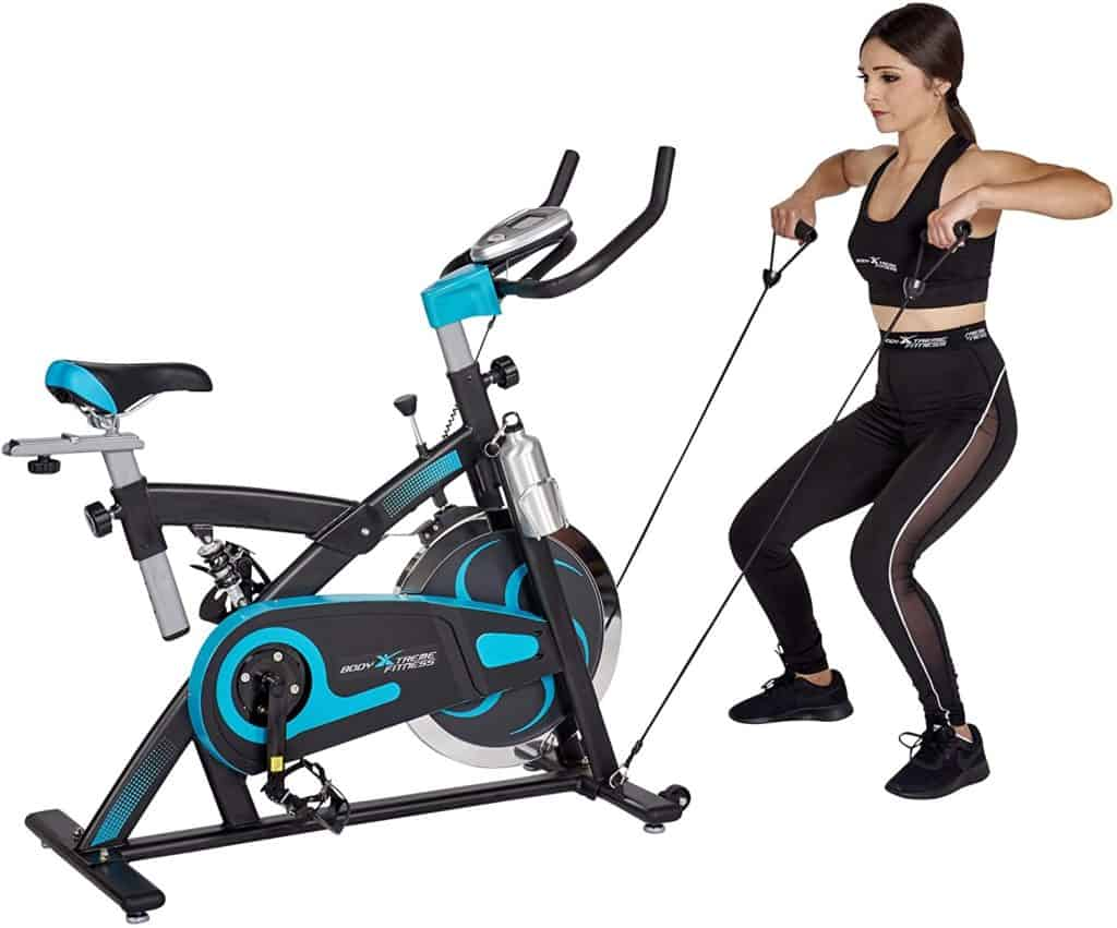 A lady is performing the upright rows with the resistance bands on the Body Xtreme Fitness Bundle BXF004 Exercise Bike