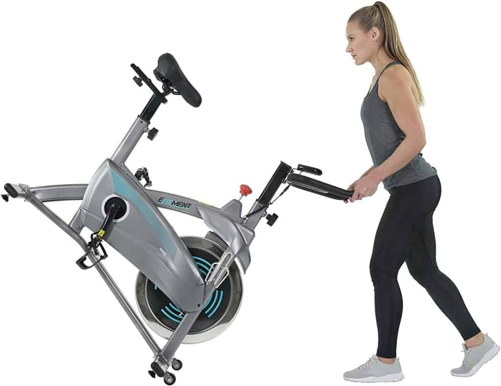 A lady moves the EFITMENT IC037 Indoor Cycling Bike to storage