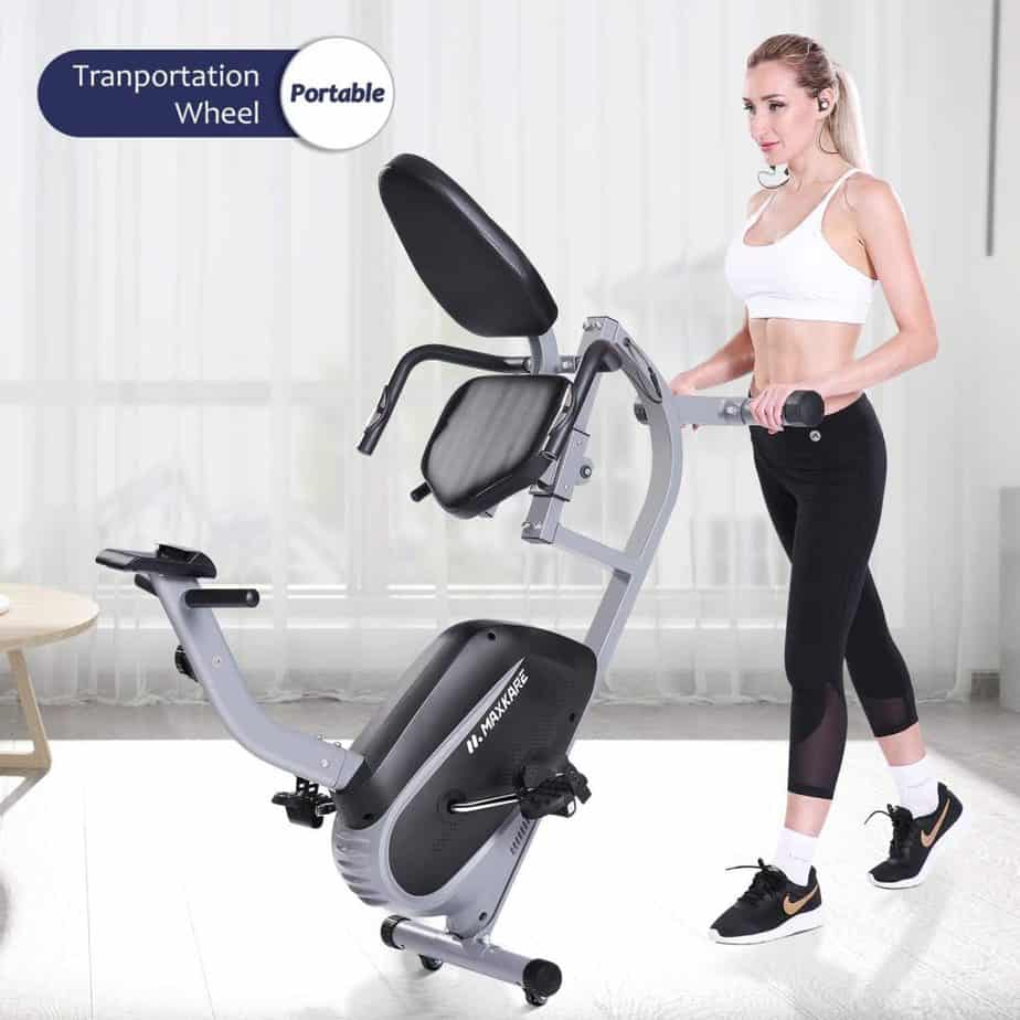 The MaxKare Recumbent Exercise Bike being rolled to storage by a lady