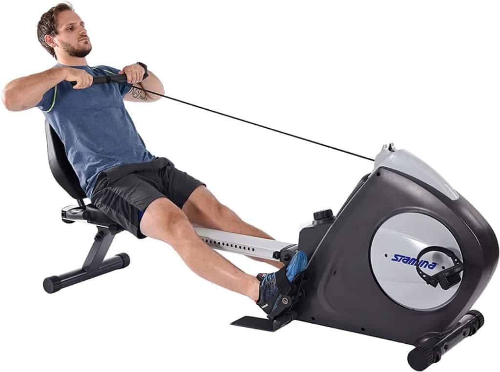 A man is rowing on the Stamina Conversion II Recumbent Bike/Rower