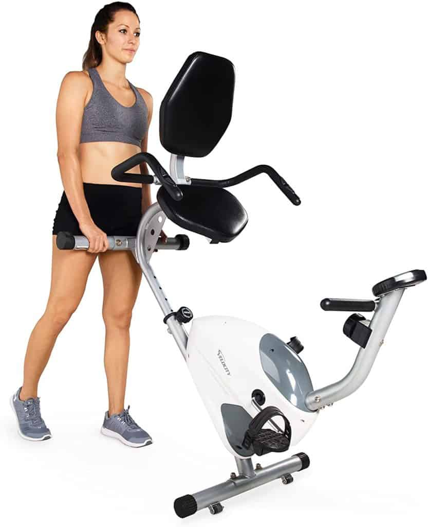 The lady rolls the Velocity Exercise CHB-R2102 Recumbent Bike away for storage