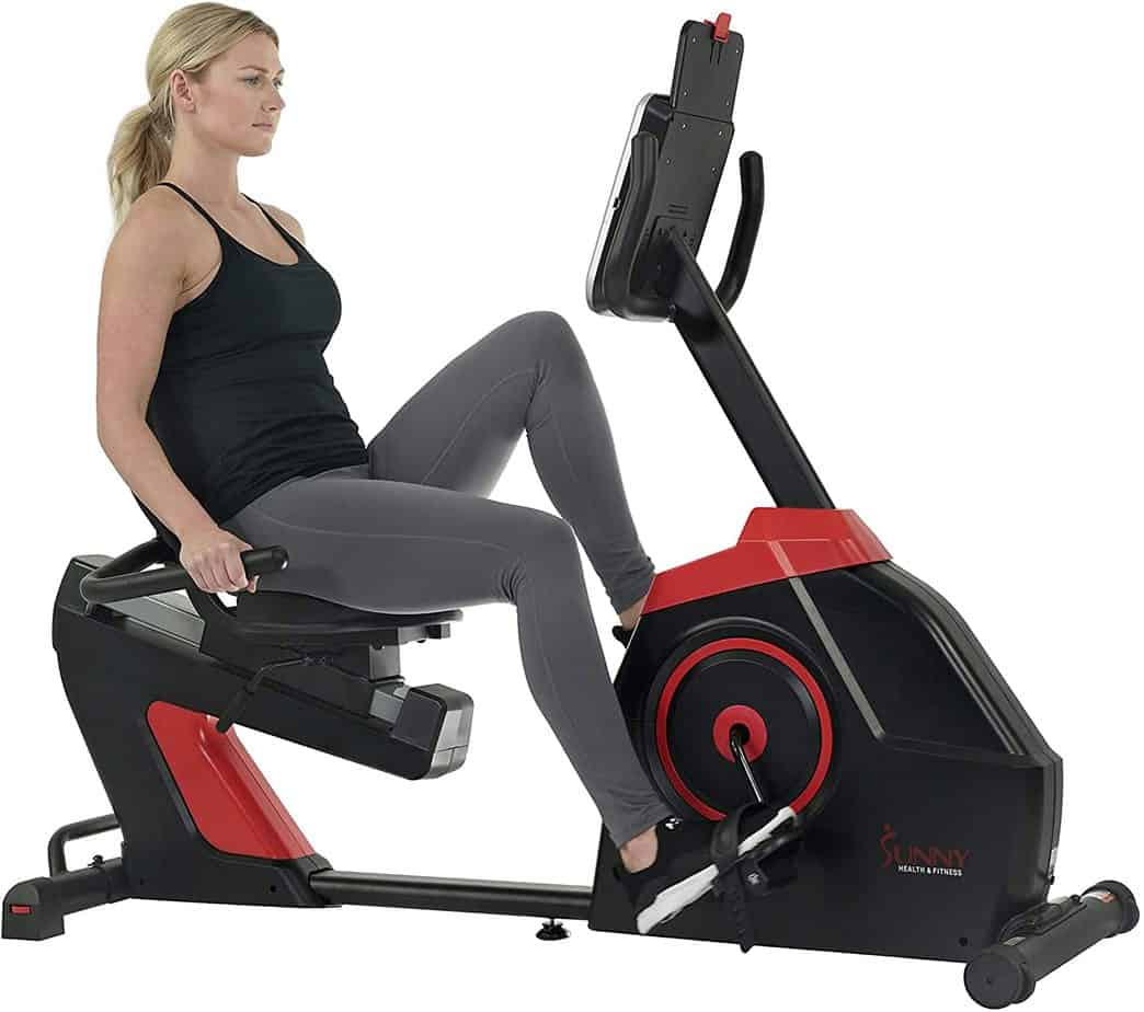 A lady is exercising with the Sunny Health & Fitness SF-RB4954 Evo-Fit Cardio Recumbent Bike