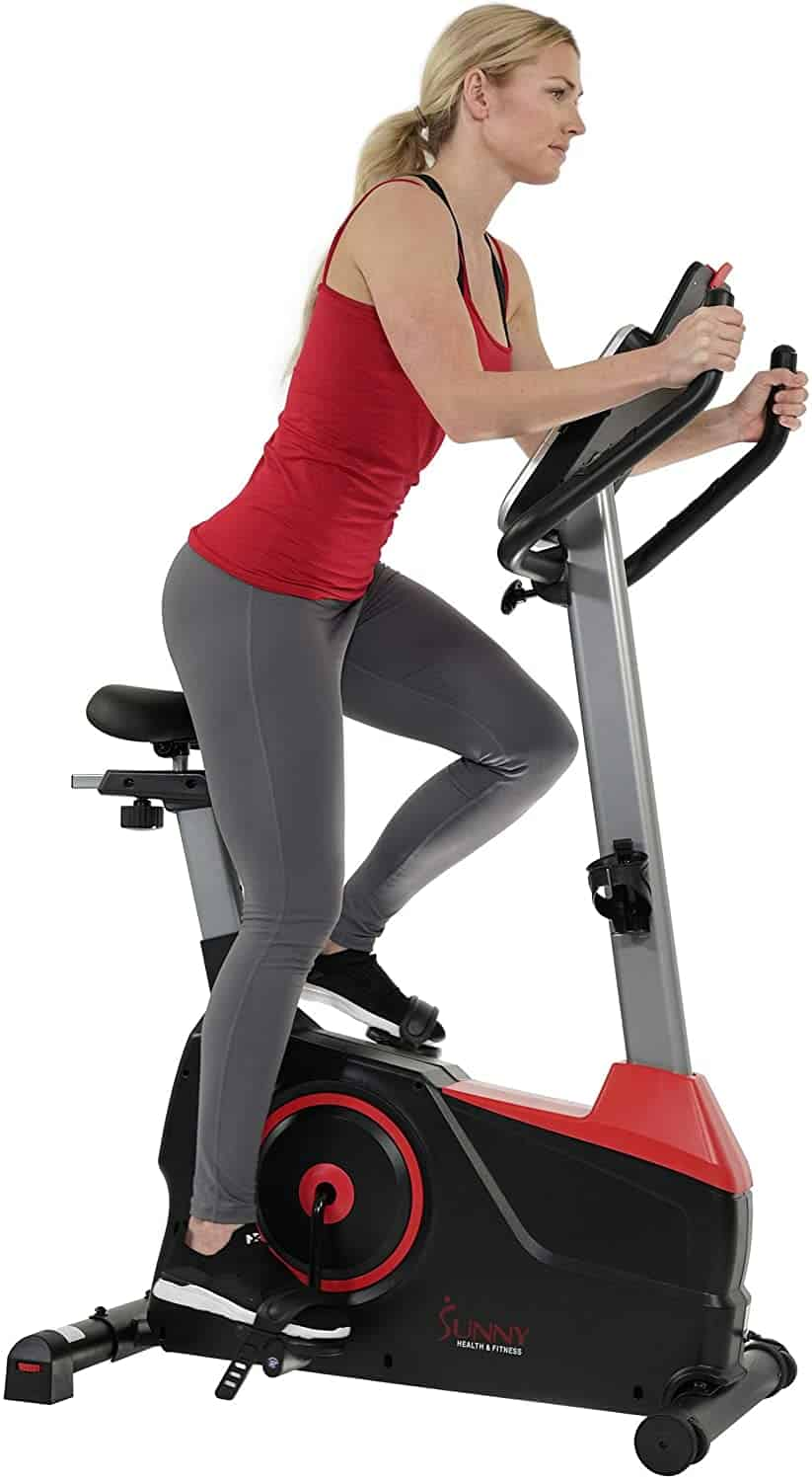A lady is exercising with the Sunny Health & Fitness Evo Fit SF-B2969 Upright Bike