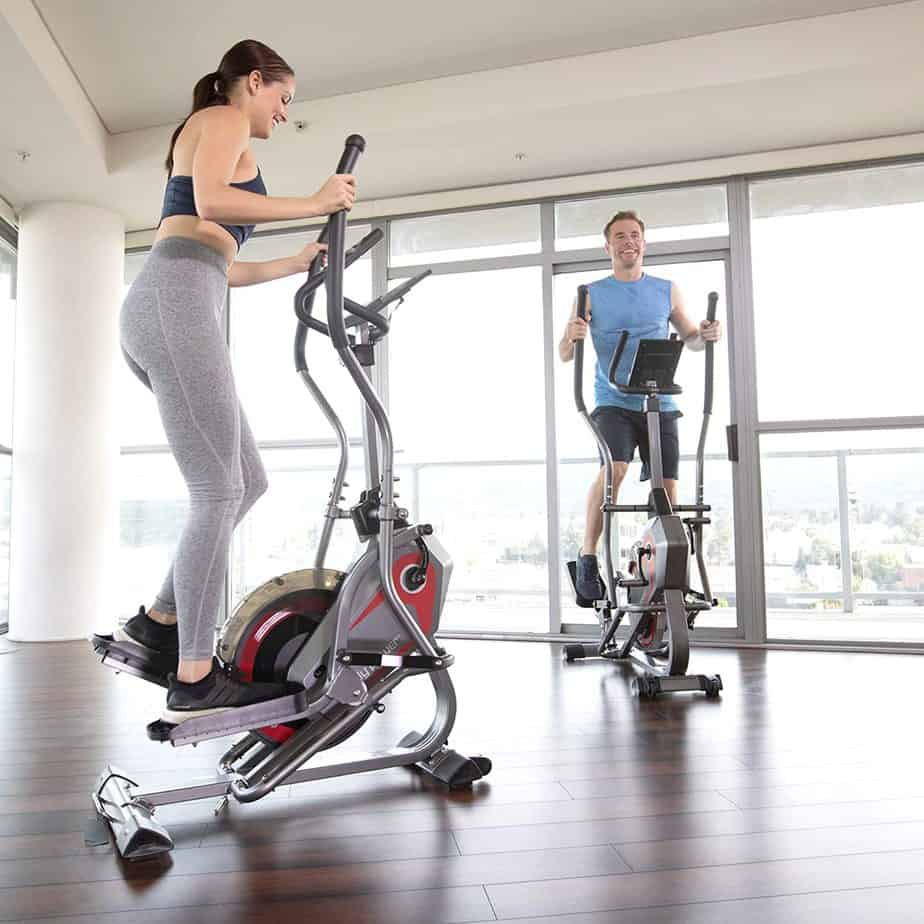 A lady and a gentle man are working out with the Body Power 2-in-1 BST800 Elliptical Stepper Trainer