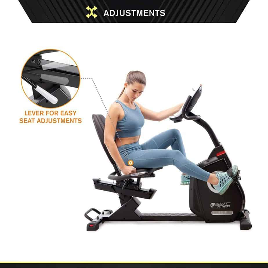 A lady working on the Circuit Fitness AMZ-587R Magnetic Recumbent Bike and also adjusting the seat