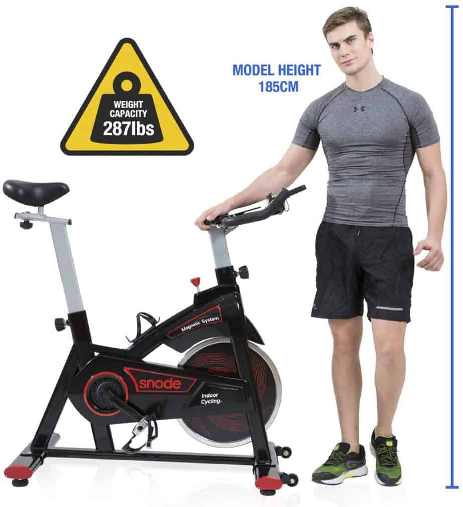 A 6' tall man standing by the SNODE 8731 Indoor Cycling Bike