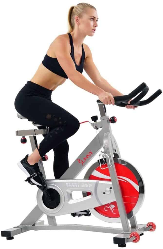 A lady rides the Sunny Health and Fitness Pro SF-B901B Indoor Cycling Bike