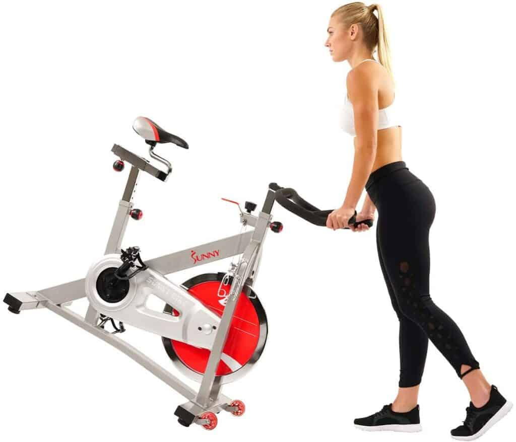 The user rolls away the Sunny Health and Fitness Pro SF-B901B Indoor Cycling Bike for storage