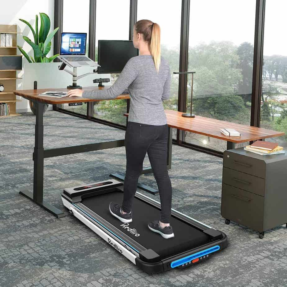 A lady walks on the Redliro Under Desk 2-in-1 Treadmill while working on the computer