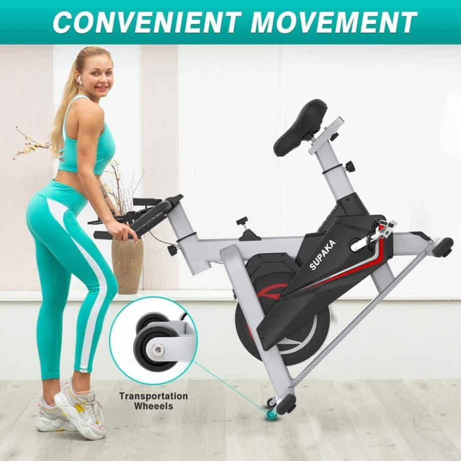A lady moves the SUPAKA Indoor Magnetic Spin Bike for storage