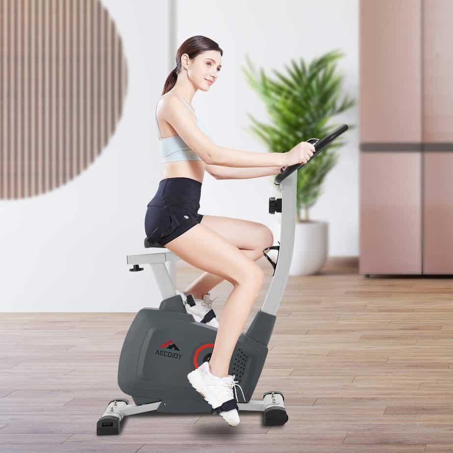 A lady exercises with the AECOJOY Upright Magnetic Exercise Bike