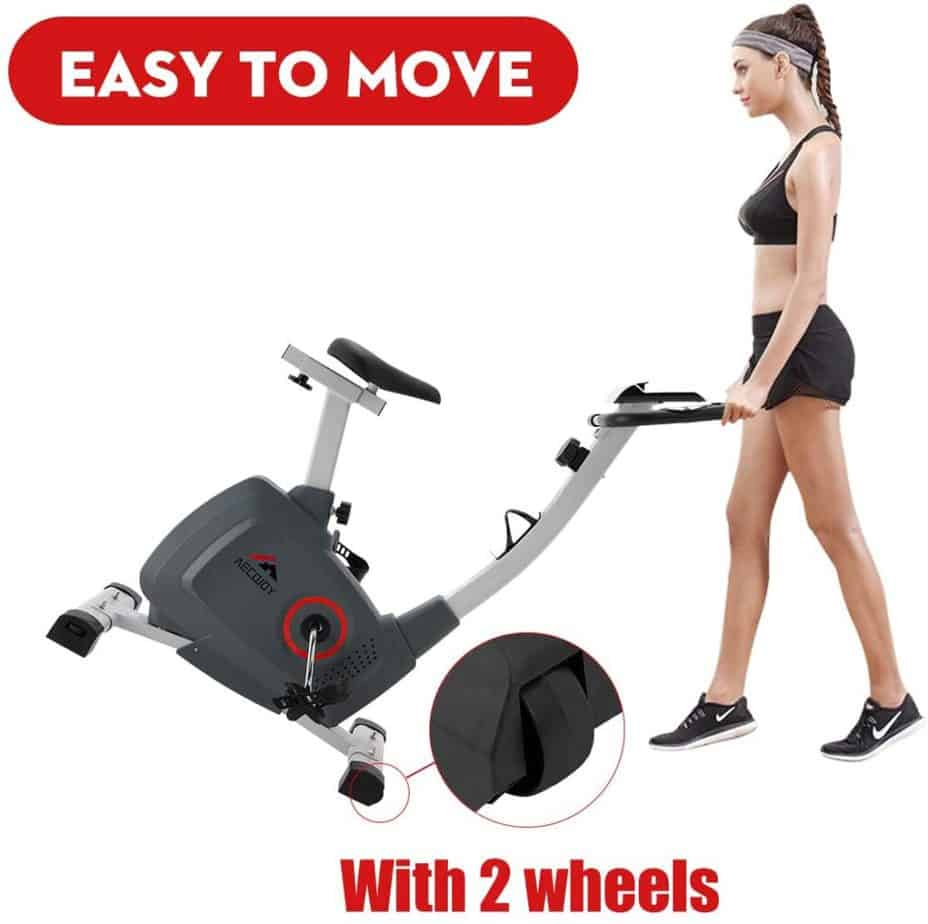 A lady moves the AECOJOY Upright Magnetic Exercise Bike to storage area