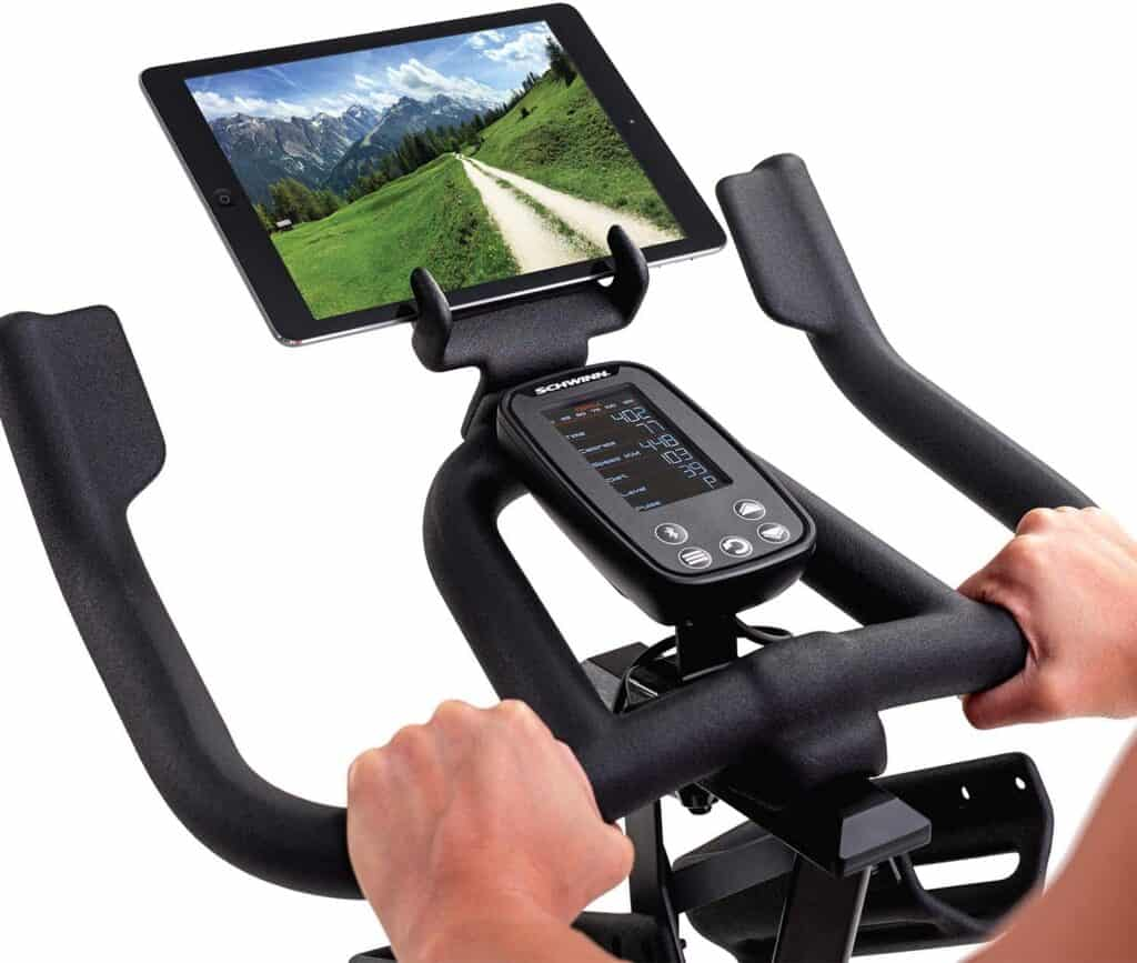 The console, and the handlebar of the Schwinn IC4 Indoor Cycling Exercise Bike with a tablet device on the holder
