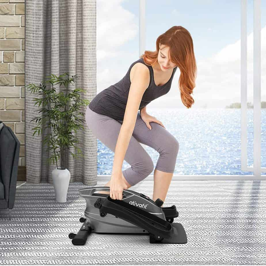 A lady lifts the Ativafit Under-Desk Elliptical Bike by the handle for storage