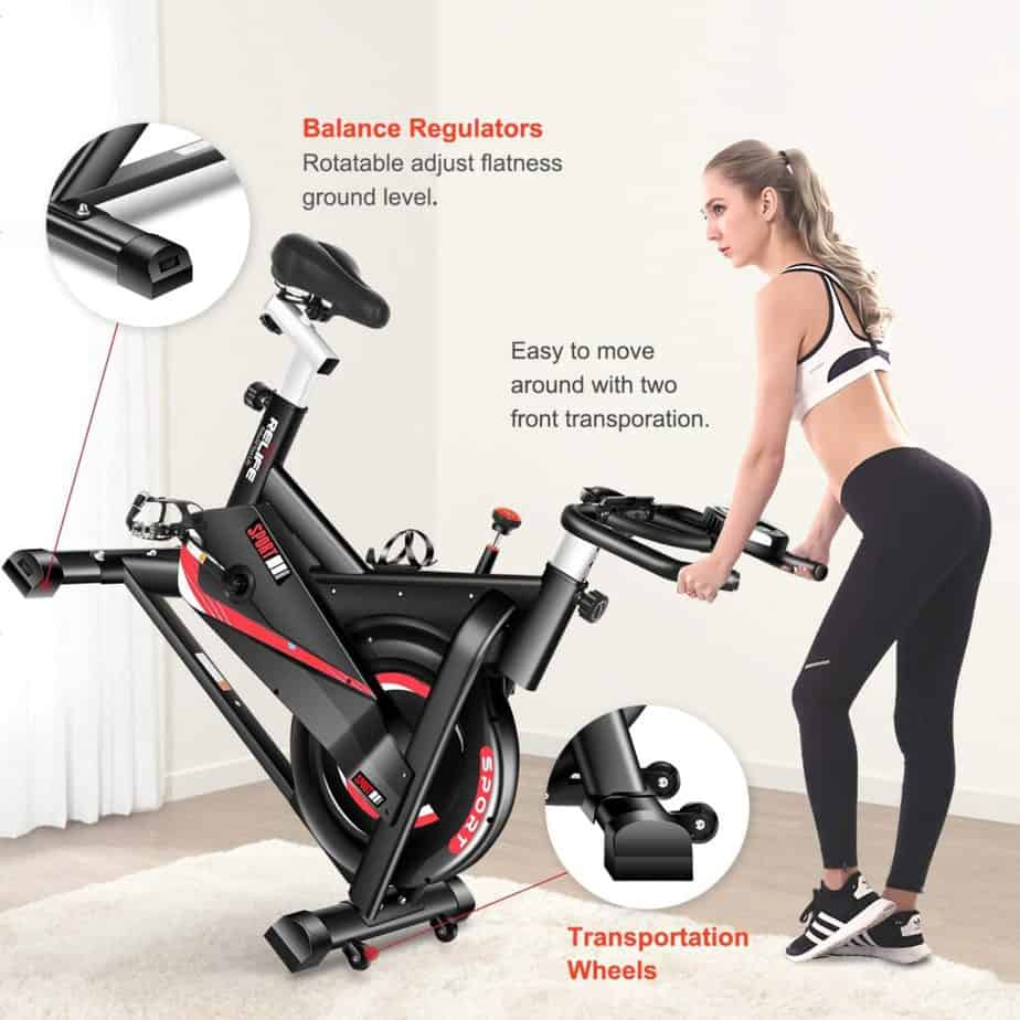 A lady moves the RELIFE REBUILD YOUR LIFE Indoor Cycling Bike for storage