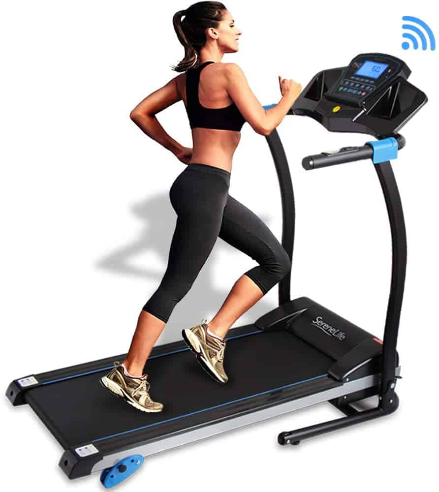 A lady runs on the SereneLife SLFTRD25 Smart Folding Treadmill
