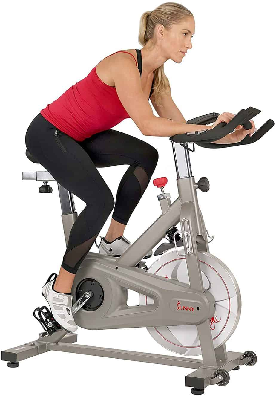 A lady exercises with the Sunny Health & Fitness SF-B1851 Synergy Pro Indoor Cycling Bike